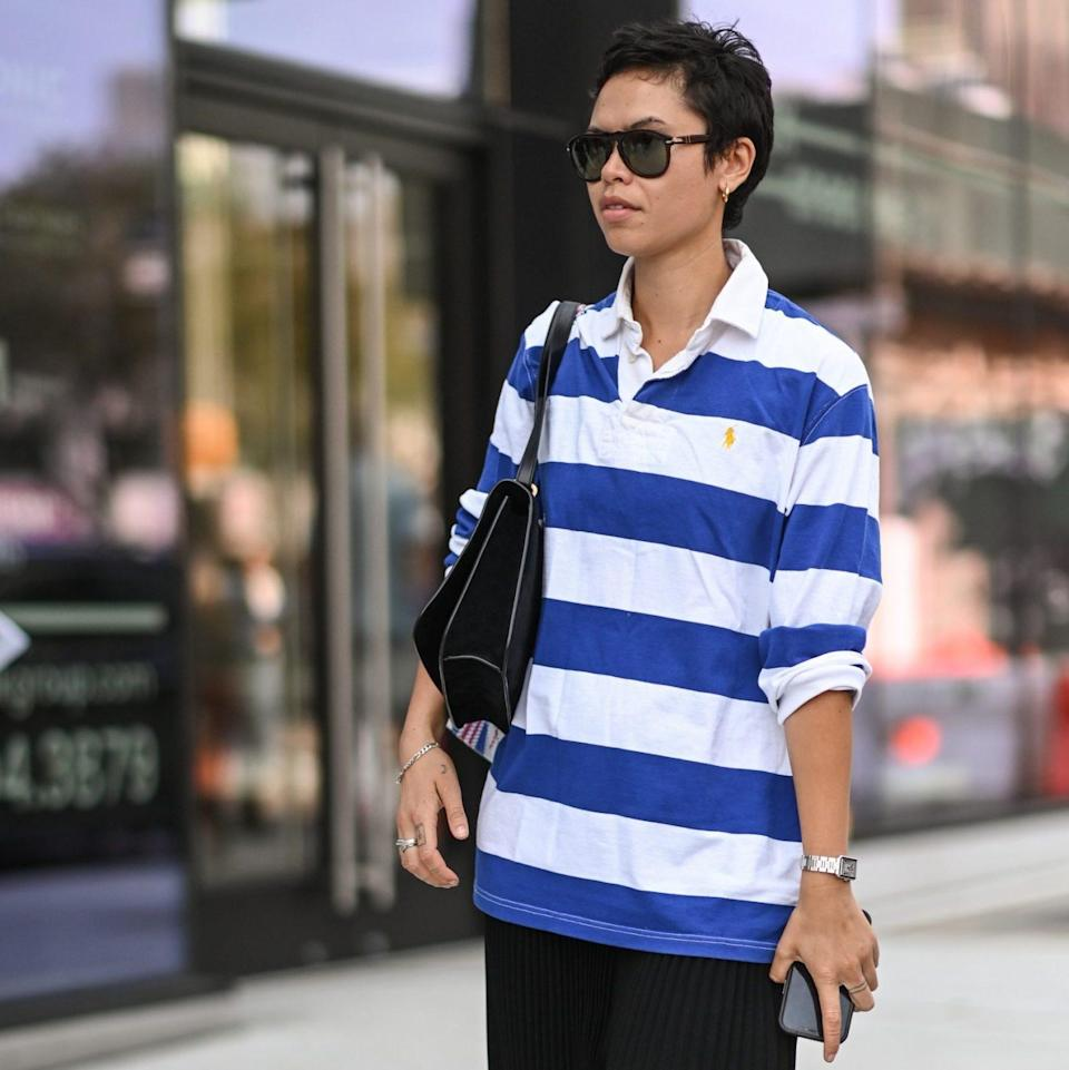 A guest is seen wearing a white and blue striped shirt and black pants with sandals outside the Khaite show - Daniel Zuchnik / Getty Images North America