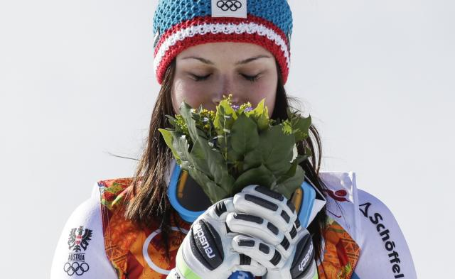 Women's super-G gold medal winner, Austria's Anna Fenninger smells her flower bouquet during the flower ceremony on the podium the Sochi 2014 Winter Olympics, Saturday, Feb. 15, 2014, in Krasnaya Polyana, Russia