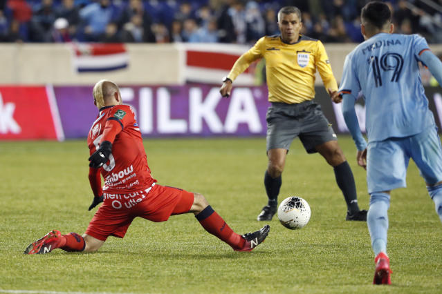 San Carlos midfielder Esteban Ramirez (5) keeps the ball from New York City FC forward Jesus Medina (19) as an official watches during the second half in the second leg of a CONCACAF Champions League soccer match Wednesday, Feb. 26, 2020, in Harrison, N.J. NYCFC won 1-0. (AP Photo/Kathy Willens)