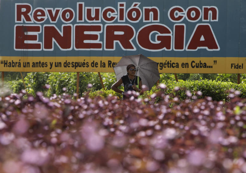 """**CORRECTS SPELLING OF CANTARRANA** In this July 18, 2013 photo, a woman holds an umbrella as protection from the sun in front of a sign that reads in Spanish; """"Energy with Revolution"""" in Cantarrana, Cuba. Cantarrana is already saving the island around $800 a day and will pay for itself after a little more than a decade into its 25-year expected lifespan. It's a notable change in the mindset for a country that relies on imports for half its energy consumption and is vulnerable to the political ebb and flow in other countries. (AP Photo/Franklin Reyes)"""