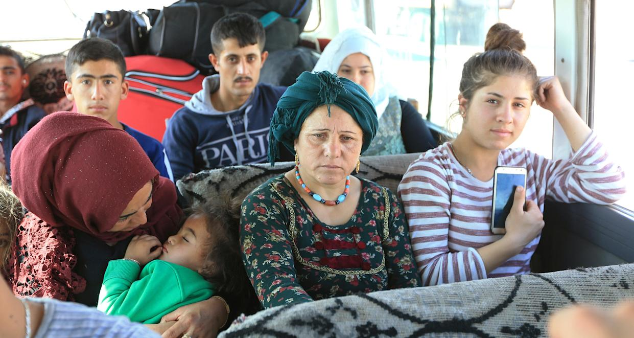 Syrian displaced families, who fled violence after the Turkish offensive against Syria, sit in a bus on their way to camps on the outskirts of Dohuk, Iraq on Oct. 16, 2019. (Photo: Ari Jalal/Reuters)