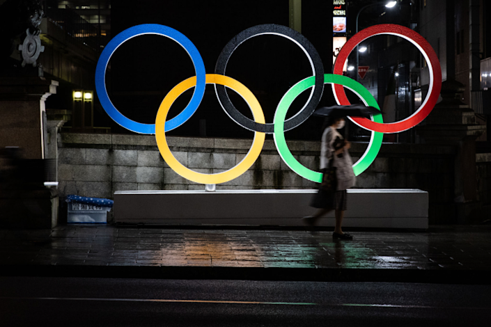 TOKYO, JAPAN - JULY 09: A woman wearing a face mask walks past the Olympic Rings on July 09, 2021 in Tokyo, Japan.
