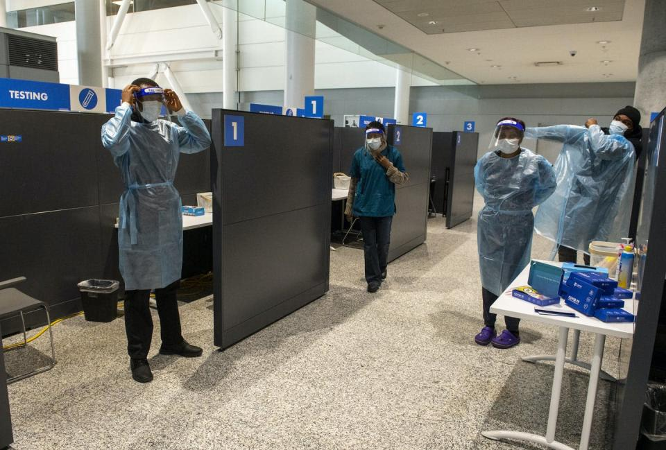 """<span class=""""caption"""">Workers prepare to greet passengers at the COVID-19 testing centre in the international arrivals area at Pearson Airport in Toronto on Jan. 26, 2021. </span> <span class=""""attribution""""><span class=""""source"""">THE CANADIAN PRESS/Frank Gunn</span></span>"""