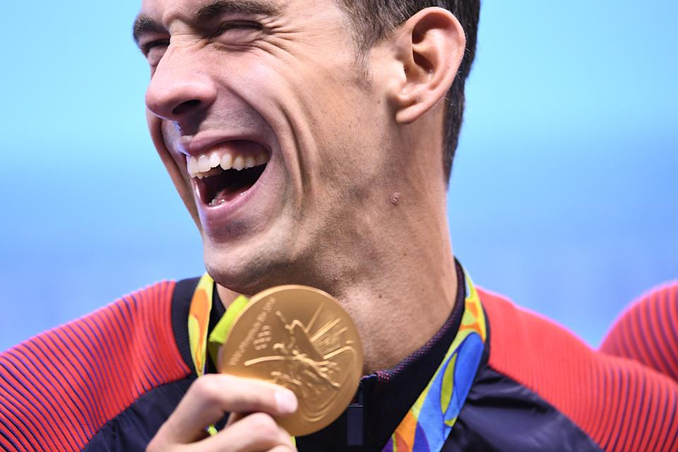 TOPSHOT - USA's Michael Phelps poses with his gold medal during the podium ceremony of the Men's swimming 4 x 100m Medley Relay Final at the Rio 2016 Olympic Games at the Olympic Aquatics Stadium in Rio de Janeiro on August 13, 2016.   Michael Phelps brought down the curtain on his glittering Olympic career when he helped the USA win 4x100m medley relay gold at the Rio Games on Saturday, taking his personal tally to 23. / AFP / GABRIEL BOUYS        (Photo credit should read GABRIEL BOUYS/AFP/Getty Images)