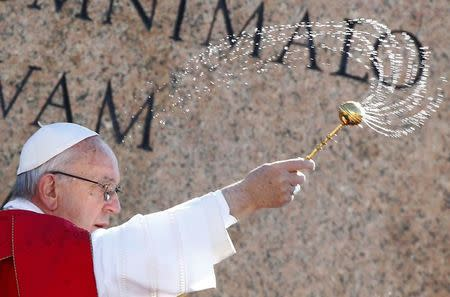 Pope Francis blesses with holy water as he leads the Palm Sunday Mass in Saint Peter's Square at the Vatican