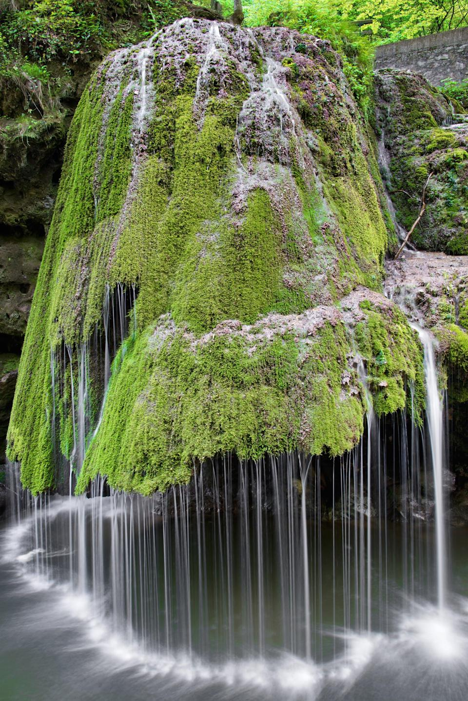 <p>One look at this waterfall and you'll see why traveling to it is a must. The stream falls from a cliff onto the moss, which makes the water fall in the interesting patterns you see. </p>