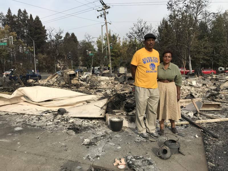 Marion and Lloid Heim stand amid the ashes of their Santa Rosa home. They had moved in just a year ago.