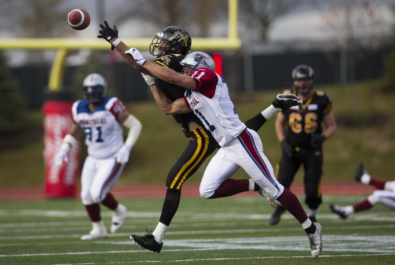 Hamilton Tiger-Cats' Andy Fantuz (C, L) reaches for a pass against Montreal Alouettes' Chip Cox (C, R) during the second half of their East semi-final CFL football in Guelph, November 10, 2013. REUTERS/Mark Blinch (CANADA - Tags: SPORT FOOTBALL TPX IMAGES OF THE DAY)