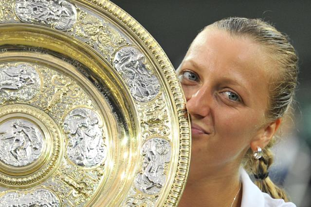 Czech Republic's Petra Kvitova kisses the winner's title after beating Canada's Eugenie Bouchard in the women's singles final on day 12 of the Wimbledon Championships at The All England Tennis Club in southwest London, on July 5, 2014 (AFP Photo/Glyn Kirk)
