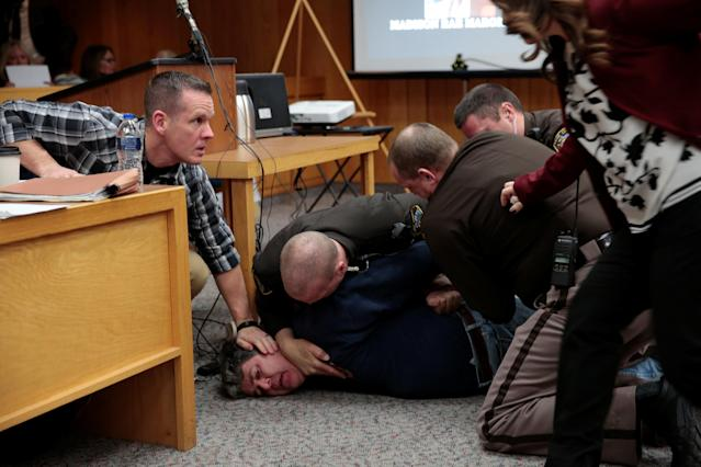 Randall Margraves (2nd L) is tackled after he lunged at Larry Nassar (not seen) a former team USA Gymnastics doctor who pleaded guilty in November 2017 to sexual assault charges, during victim statements of his sentencing in the Eaton County Circuit Court in Charlotte, Michigan, U.S., February 2, 2018. Picture 8 of 10 in series. REUTERS/Rebecca Cook