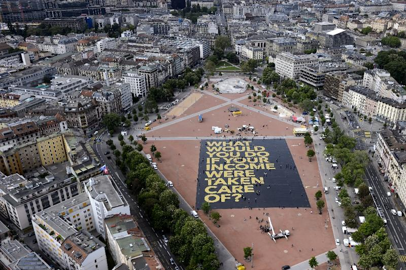"""A giant poster reading: """"What would you do if your income was taken care of?"""" is laid out on May 14, 2016 in Plainpalais Place in Geneva (AFP Photo/Fabrice Coffrini)"""