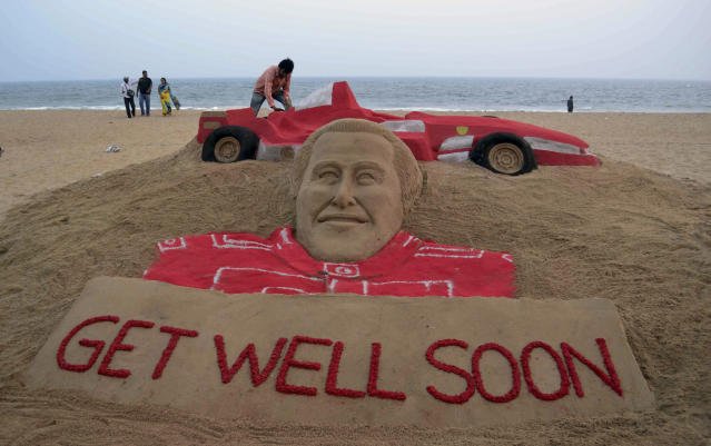 Visitors gather near a sculpture of Formula One great Michael Schumacher titled Get Well Soon by sand artist Sudarshan Patnaik at a beach in Puri, in the eastern Indian city of Bhubaneswar, India, Friday, Jan. 3, 2014. Schumacher has been in a medically induced coma since Sunday, when he struck his head on a rock while on a family skiing vacation. (AP Photo/Biswaranjan Rout)