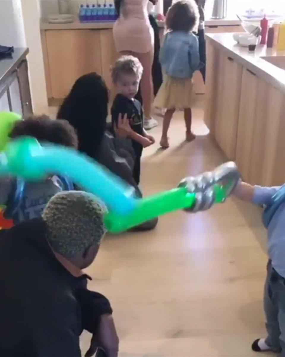 """Kanye bends down to play with the kids in one video taken in their kitchen, which shows off their pale wood cabinetry and hardwood floors. Kim told <em>AD</em> that she and Kanye <a href=""""https://people.com/home/kim-kardashian-west-reveals-how-she-and-kanye-keep-their-white-furniture-safe-from-their-kids/"""" rel=""""nofollow noopener"""" target=""""_blank"""" data-ylk=""""slk:designed the house with their kids in mind"""" class=""""link rapid-noclick-resp"""">designed the house with their kids in mind</a>, despite its almost all-white interior. """"We decided we wanted a house that didn't need baby-proofing,"""" she said of much of the home's round-edged furniture."""
