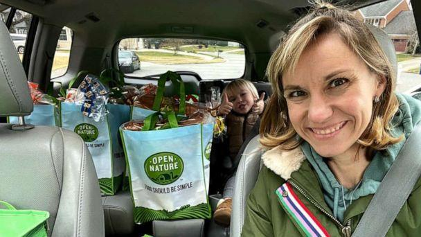 PHOTO: Amber Marchand and her son pose in the car with food they have collected for charity. (Amber and Sterling Marchand/Be The Good Project)