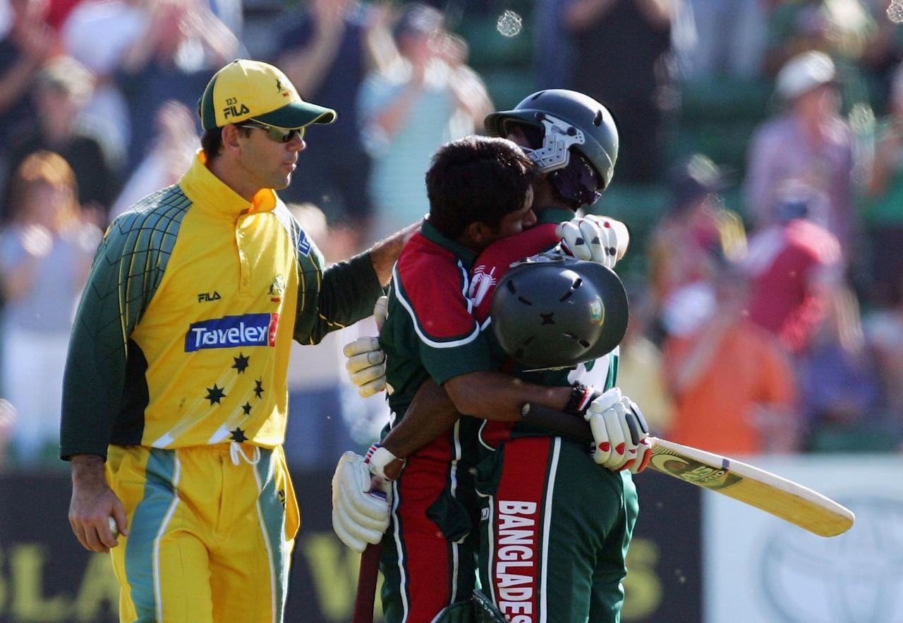 Mohammad Ashraful (centre) of Bangladesh hugs team mate Aftab Ahmed Chowdhury while he is congratulated on his century by Ricky Ponting of Australia during the NatWest Series One Day International between Australia and Bangladesh played at Sophia Gardens on June 18, 2005 in Cardiff, United Kingdom  (Photo by Hamish Blair/Getty Images)