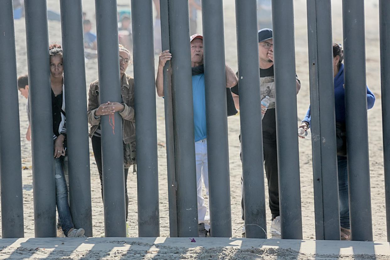 Honduran caravan members at the fence at the U.S.-Mexico border wall at Friendship Park in San Ysidro, Calif., on Monday. (Photo: Sandy Huffaker / AFP/Getty Images)