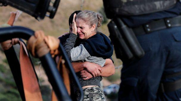 PHOTO: Framed by heavily armed Mexican authorities, relatives of the LeBaron family mourn at the site where nine U.S. citizens, were killed, at the Sonora-Chihuahua border, Mexico, Nov 6, 2019. (Marco Ugarte/AP)