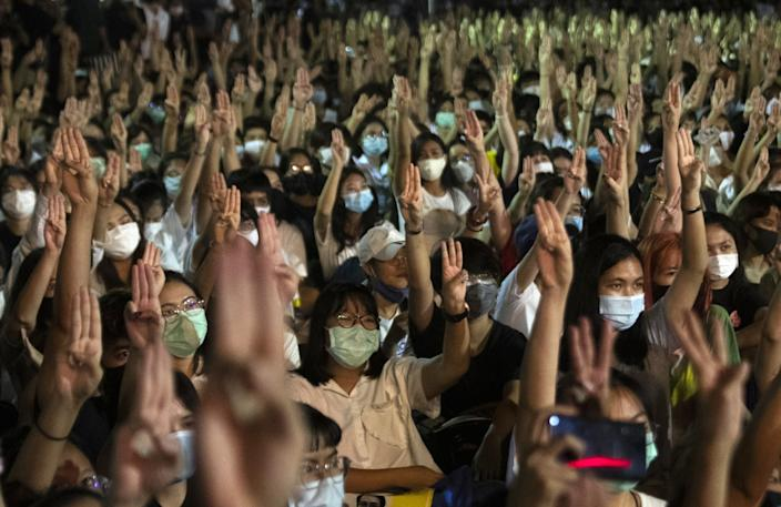Thai student protesters raise a three-finger salute.