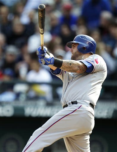 Texas Rangers' Mike Napoli hits a solo home run against the Seattle Mariners in the fourth inning of a baseball game, Sunday, Sept. 23, 2012, in Seattle. (AP Photo/Ted S. Warren)