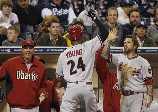 Arizona Diamondbacks' Chris Young high fives with teammate Ryan Roberts, right, upon rreturning to the dugout after his two run homer in the 11th inning against the San Diego Padres in a baseball game Tuesday, April 10, 2012 in San Diego. Manager Kirk Gibson is left. (AP Photo/Lenny Ignelzi)