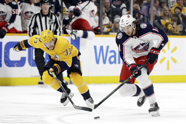 Columbus Blue Jackets center Kevin Stenlund (11) moves the puck ahead of Nashville Predators right wing Viktor Arvidsson (33), of Sweden, in the first period of an NHL hockey game Saturday, Feb. 22, 2020, in Nashville, Tenn. (AP Photo/Mark Humphrey)