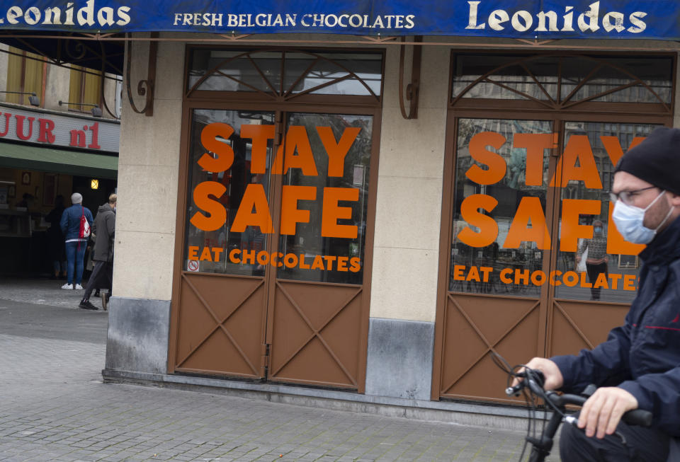 A man cycles by a chocolate shop with a message in the window in the historic center of Antwerp, Belgium, Sunday, Oct. 18, 2020. Faced with a resurgence of coronavirus cases, the Belgian government on Friday announced new restrictions to try to hold the disease in check, including a night-time curfew and the closure of cafes, bars and restaurants for a month. The measures will take effect on Monday, Oct. 19, 2020. (AP Photo/Virginia Mayo)