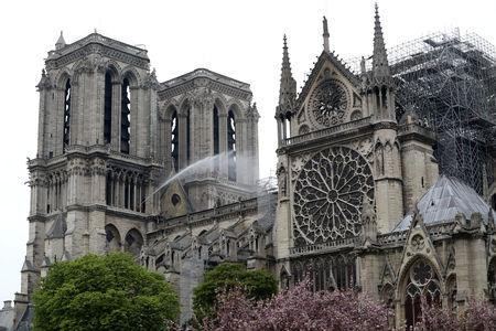 Firefighters work at Notre-Dame Cathedral after a massive fire devastated large parts of the gothic gem in Paris