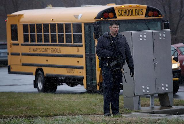 <p>A heavily armed law enforcement officer stands guard as students from Great Mills High School are evacuated to Leonardtown High School following a school shooting at Great Mills High School March 20, 2018 in Leonardtown, Maryland. (Photo: Win McNamee/Getty Images) </p>