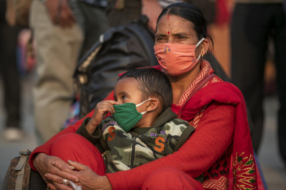 A Nepalese woman with her child waits for a bus to go back to her village a day prior to lockdown in Kathmandu, Nepal, Wednesday, April 28, 2021. Tens of thousands of people left the Nepalese capital Wednesday a day ahead of a 15-day lockdown imposed by the government because of spiking cases of COVID-19 in the country. The lockdown has been imposed in most of the major cities and towns in the country. (AP Photo/Niranjan Shrestha)