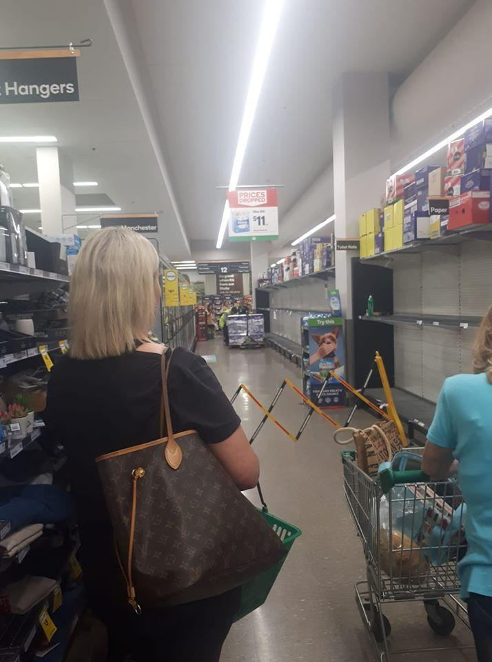 The woman shared a photo of the Woolworths putting up a barrier to allow staff to stock the shelves with toilet paper. Source: Facebook