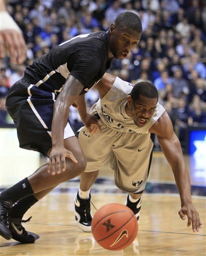 Gonzaga guard Gary Bell Jr., left, and Xavier guard Tu Holloway chase a loose ball in the first half of an NCAA college basketball game on Saturday, Dec. 31, 2011, in Cincinnati. (AP Photo/Al Behrman)