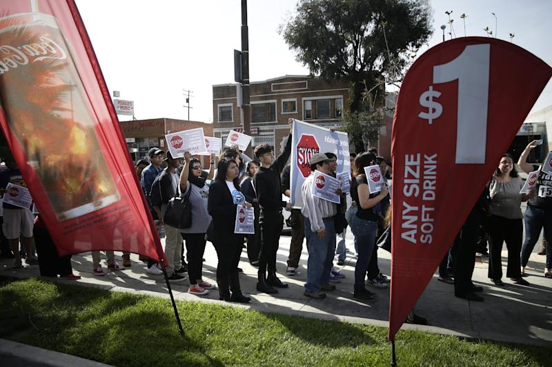 Demonstrators hold signs and banners during a protest outside a McDonald's restaurant on Tuesday, March 18, 2014, in Huntington Park, Calif. Protesters were set to rally outside McDonald's restaurants in cities including Boston, Chicago and Miami to call attention to the denial of overtime pay and other violations they say deprive workers of the money they're owed. (AP Photo/Jae C. Hong)