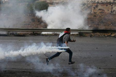 A Palestinian protester runs to return a teargas canister fired by Israeli troops during clashes near the Jewish settlement of Bet El, near the West Bank city of Ramallah, October 29, 2015. REUTERS/Mohamad Torokman