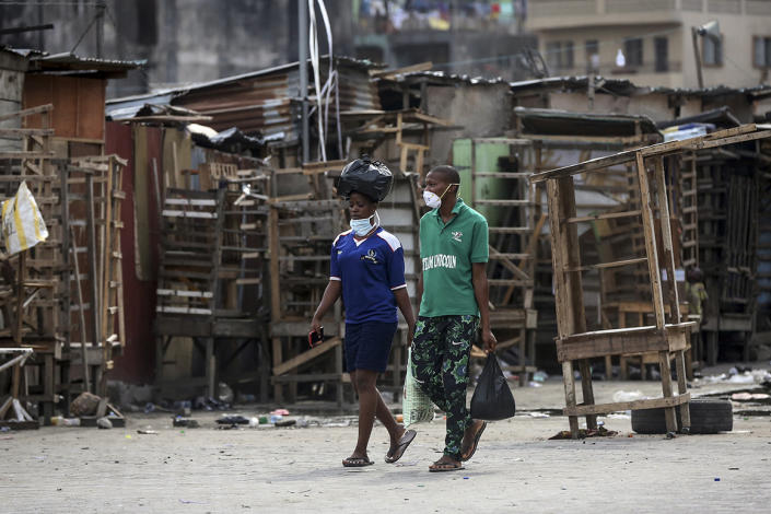People walk past closed street stalls and shops due to a government ban on the operation of non-essential businesses and markets to halt the spread of the new coronavirus, in Lagos, Nigeria, on March 26, 2020.