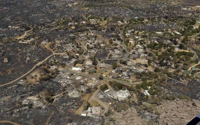 Several homes are seen destroyed by fire in Yarnell, Ariz., Sunday, July 7, 2013. Nineteen elite firefighters were overtaken by the out-of-control blaze in the area as they tried to protect themselves from the flames under fire-resistant shields. (AP Photo/Mark J. Terrill)