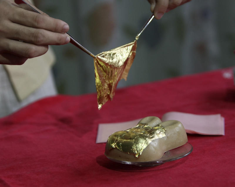 Entrepreneur Angelito Araneta Jr. wraps a rabbit-shaped sweet rice cake, locally known as Tikoy, with a 24-carat edible gold leaf before encrusting with a 0.2-carat diamond Wednesday, Feb. 2, 2011 at his home in Manila, Philippines. The gold and diamond encrusted sweet rice cake sells for 21,500 pesos ($485) and is one of 13 ordered by rich Chinese customers for the celebration of the lunar new year, the Year of the Rabbit in Chinese calendar. Araneta Jr. said one customer he catered, ordered for a two-diamond gold encrusted rice cake which is priced for 120,000 pesos ($2,710), his most expensive so far. (AP Photo/Bullit Marquez)