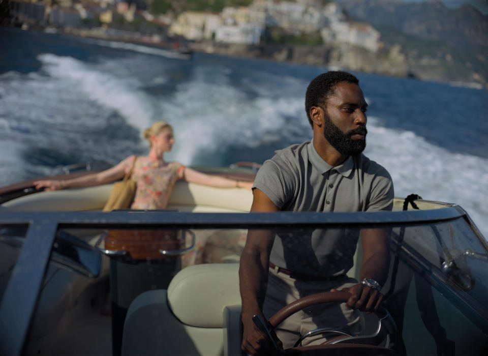 """This image released by Warner Bros. Entertainment shows Elizabeth Debicki, left, and John David Washington in a scene from """"Tenet."""" Warner Bros. says it is delaying the release of Christopher Nolan's sci-fi thriller """"Tenet"""" until Aug. 12. (Melinda Sue Gordon/Warner Bros. Entertainment via AP)"""