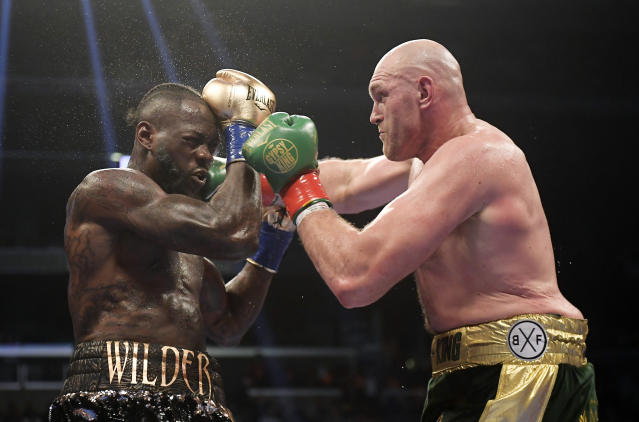 FILE - In this Dec. 1, 2018, file photo, Tyson Fury, right, of England, connects with Deontay Wilder during a WBC heavyweight championship boxing match in Los Angeles. Wilder is still frustrated by the way he fought in his draw with Fury. The WBC heavyweight champion watched a replay of the fight for the first time Thursday, Dec. 6, 2018, and saw things he did incorrectly. (AP Photo/Mark J. Terrill, File)