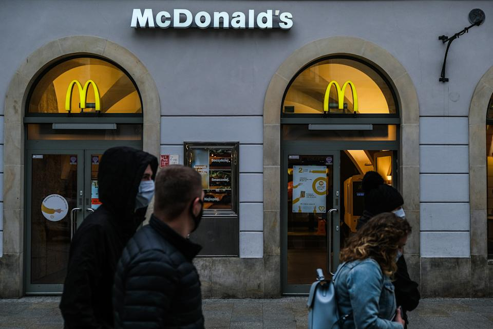 KRAKOW, POLAND - 2020/11/12: People wearing face masks as a precaution walking past the Mcdonald's closed store in Florianska street during the covid-19 pandemic. Poland is now passing through the second wave of coronavirus and introduces new restrictive measures such as the closure of stores inside shopping malls, gatherings with a maximum of 5 people, bars and restaurants operating on a takeaway basis among others. Poland has registered more than 615,000 COVID-19 infections and a death toll above 8000. (Photo by Omar Marques/SOPA Images/LightRocket via Getty Images)