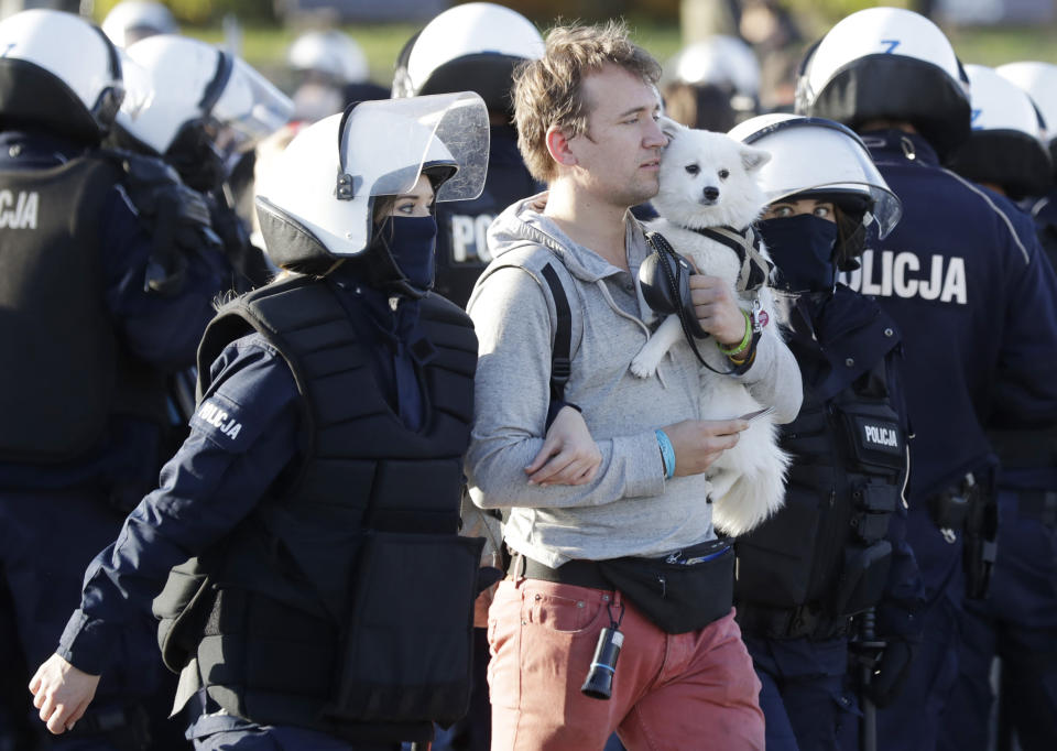 Police detain a man with a dog, in Warsaw, Poland, Saturday, Oct. 24, 2020. The man was among protesters angry at new restrictions aimed at fighting the coronavirus pandemic. The clashes come amid rising social tensions and as new restrictions just short of a full lockdown took effect Saturday.(AP Photo/Czarek Sokolowski)