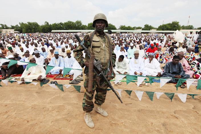"""A Nigerian soldier provides security during Eid al-Fitr prayers at Ramat square in Maiduguri, Nigeria, Thursday, Aug. 8, 2013. Nigerians in the birthplace of an Islamic uprising gripping the northeast celebrated the Muslim holy day of Eid al-Fitr on Thursday with devout prayers and a joyful show of adulation for their king that attracted more than 10,000 people. It was the first durbar in three years in the city of Maiduguri and the joy that it could take place - albeit amid massive security - was heard in the cries of ululating women, screams of delight from children and men chanting """"Long live the king!"""" (AP Photo/Sunday Alamba)"""
