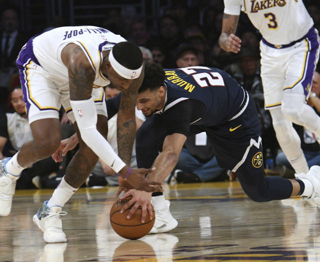 Los Angeles Lakers guard Kentavious Caldwell-Pope, left, and Denver Nuggets guard Jamal Murray reach for a loose ball during the first half of an NBA basketball game Sunday, Dec. 22, 2019, in Los Angeles. (AP Photo/Michael Owen Baker)