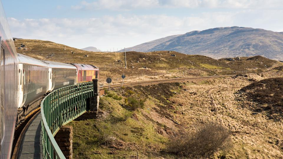 Rannoch, Scotland - May 11, 2016: Lit by the rising sun, the Caledonian Sleeper train crosses Rannoch Viaduct on the scenic West Highland Line railway in the Scottish Highlands.
