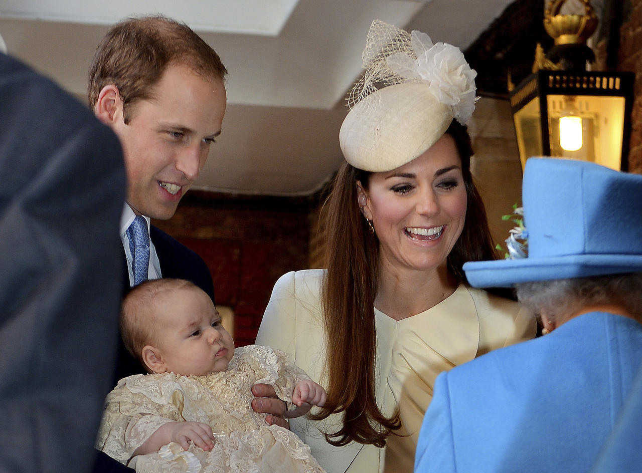 Britain's Queen Elizabeth II, right, speaks with Prince William and Kate Duchess of Cambridge as they arrive with their son Prince George at the Chapel Royal in St James's Palace, Wednesday Oct. 23, 2013. Britain's 3-month-old future monarch, Prince George will be christened Wednesday with water from the River Jordan at a rare four-generation gathering of the royal family in London. (AP Photo/John Stillwell/Pool)