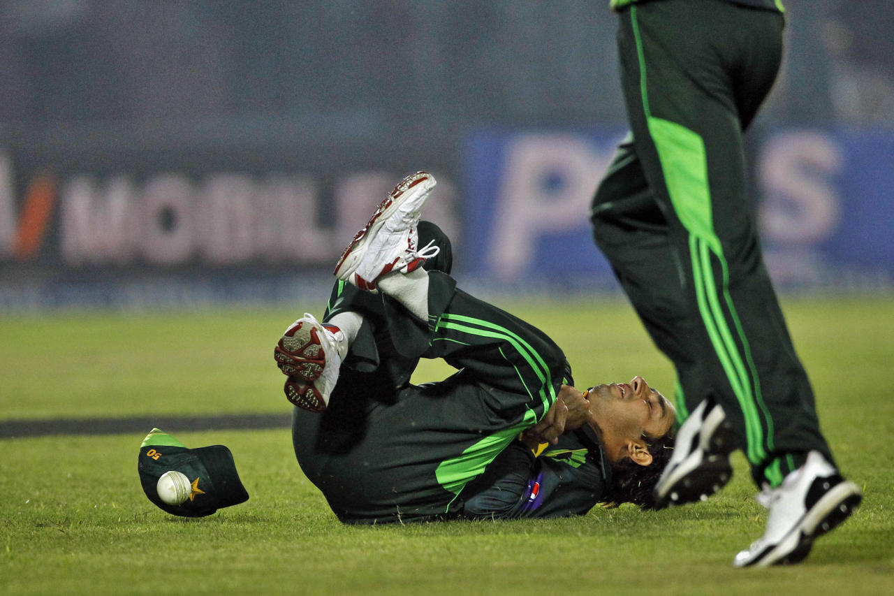 Pakistan's Saeed Ajmal dives to catch the ball while fielding during the Asia Cup one-day international cricket tournament against Afghanistan in Fatullah, near Dhaka, Bangladesh, Thursday, Feb. 27, 2014. Pakistan won by 72 runs. (AP Photo/A.M. Ahad)