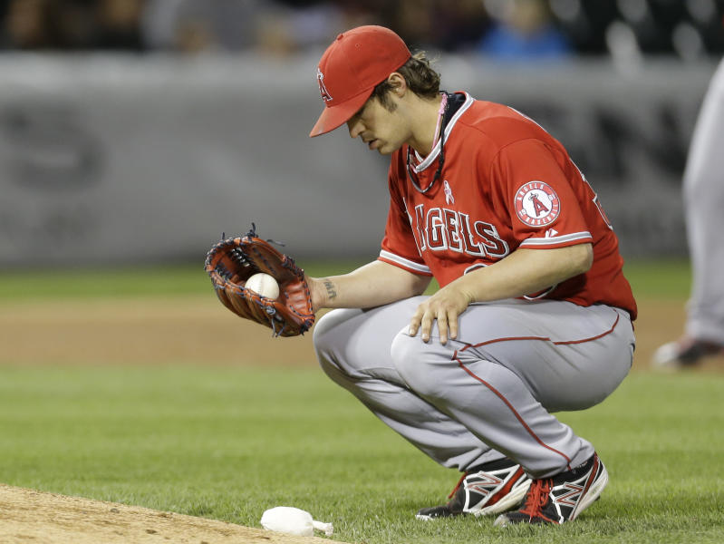 Los Angeles Angels starter C.J. Wilson reacts after throwing a wild pitch during the seventh inning of a baseball game against the Chicago White Sox in Chicago, Sunday, May 12, 2013. (AP Photo/Nam Y. Huh)