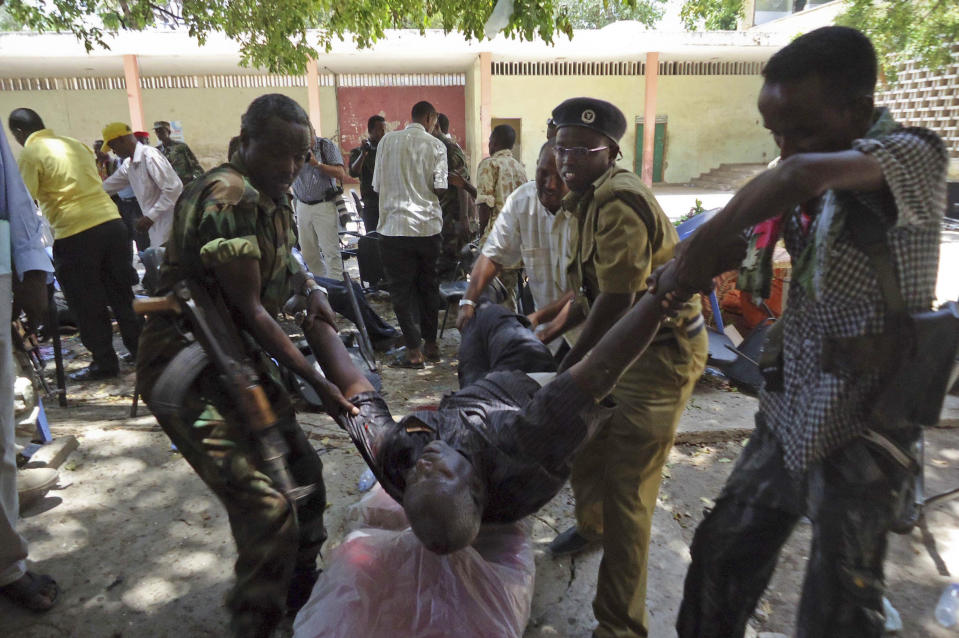 Somalis help a man wounded in a blast at the Somali National Theater in Mogadishu, Somalia Wednesday, April 4, 2012. An explosion Wednesday at a ceremony at Somalia's national theater killed at least 10 people including two top sports officials in an attack by an Islamist group on a site that symbolized the city's attempt to rise from two decades of war. (AP Photo/Farah Abdi Warsameh)