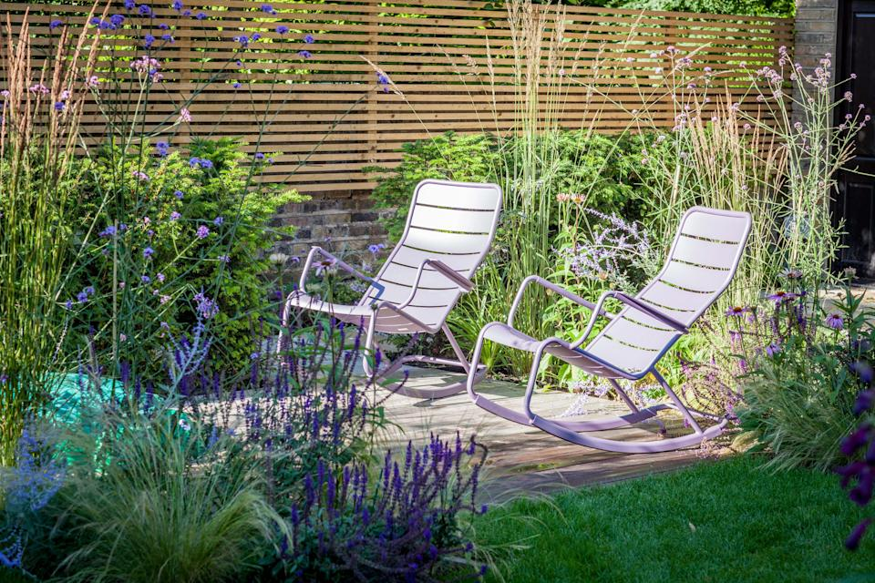 Verbena bonariensis and Salvia caradonna, along with ornamental grasses, fringe a seating area in a London garden designed by Barbara Samitier