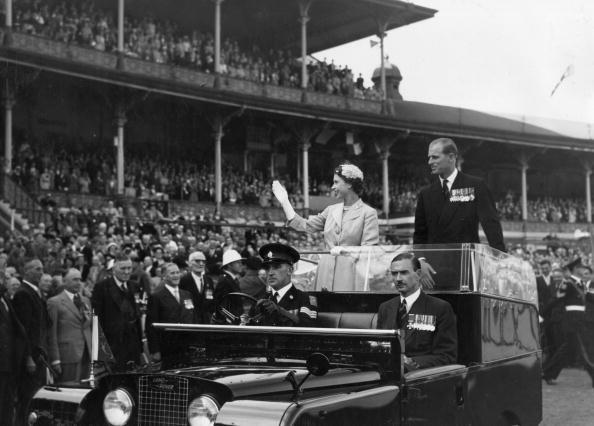 25th February 1954:  Queen Elizabeth II and Prince Philip wave to crowds as they are driven on a circuit of  Melbourne cricket ground as part of their Australian tour. The crowd comprises mainly  of ex-servicemen and war widows.  (Photo by Fox Photos/Getty Images)