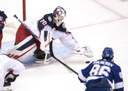 Columbus Blue Jackets goaltender Joonas Korpisalo (70) covers the puck under pressure from Tampa Bay Lightning right wing Nikita Kucherov (86) during the first period in Game 1 of an NHL hockey Stanley Cup first-round playoff series, Tuesday, Aug. 11, 2020, in Toronto. (Frank Gunn/The Canadian Press via AP)